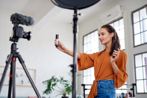 emale influencer showing product while recording video, promoting advertising using social media platforms