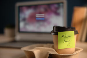 Closeup of Welcome Note on Takeaway Coffee Cup in Office Desk. Message from a Colleague or Boss